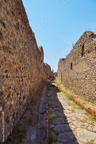 Foto  Old historical walls with alley and clear blue sky in Pompeii, Italy
