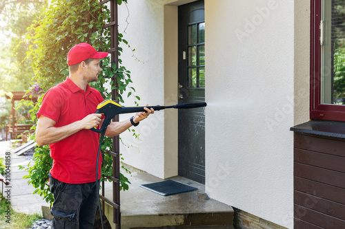 worker with high pressure washer cleaning house facade - fototapety na wymiar