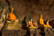 golden buddha statues along the wall inside the cave