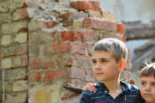 Photo Two brothers stand in an embrace, orphans are left without housing and stand near the ruins of the building as a result of a military conflict, a fire and an earthquake