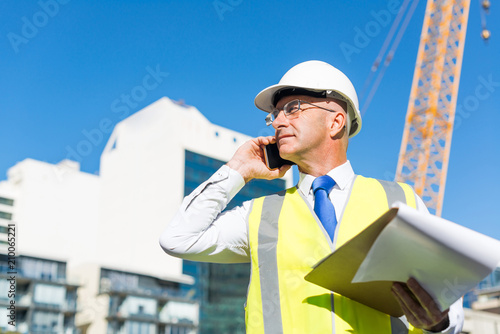 Man architector outdoor at construction area having mobile conversation Canvas Print