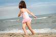 little girl is playing on the sand at the beach in the summer