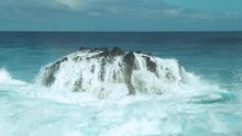 SLOW MOTION: Foaming White Seawater Flows Down A Big Black Rock In Emerald Ocean. Spectacular Shot Of Crystal Clear Waves Punishing A Large Rock Near The Tropical Rocky Shores Of The Easter Island.