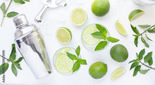 Refreshing mint alcohol cocktail mojito with rum and lime, cold drink or beverage with ice, juice, soda water, shaker and bar utensils on white table Wallpaper Mural