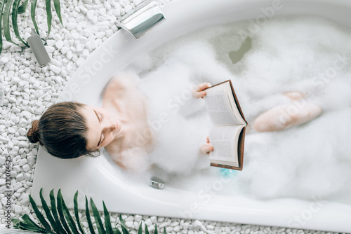 Foto Woman lying in bath with foam and reads magazine