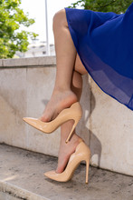 Young Woman Feet While Dangling Her High Heel Shoes In Waiting Pose