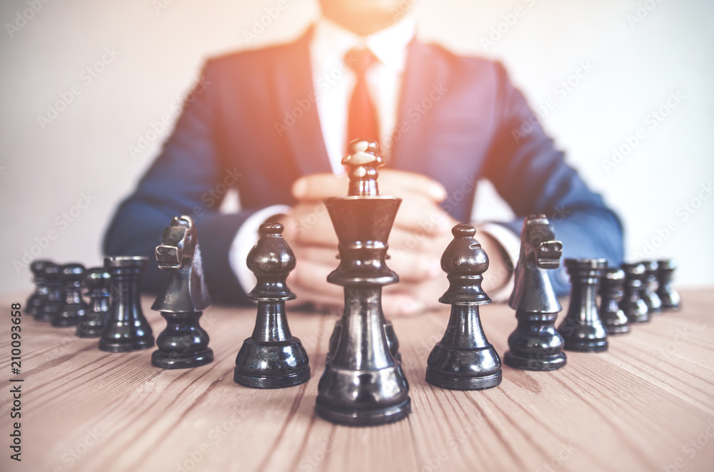 Fototapeta Retro style image of a businessman with clasped hands planning strategy with chess figures on an old wooden table.