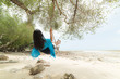 Beautiful woman relaxing on wooden swing under tree on tropical beach, Koh Samet island, Rayong, Thailand