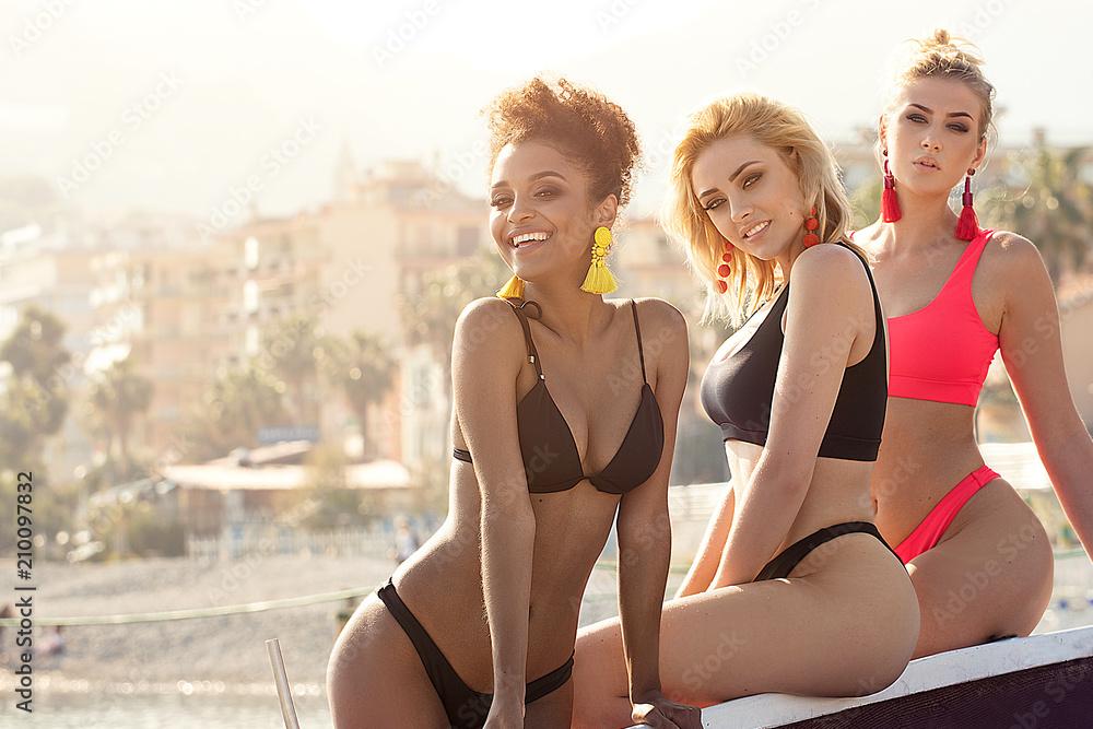 Fototapeta Three smiling happy girls posing in bikini.
