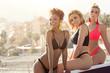 Leinwandbild Motiv Three smiling happy girls posing in bikini.