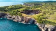 An epic aerial shot off a huge cliff in shore in Nusa Penida island in Bali Indonesia.