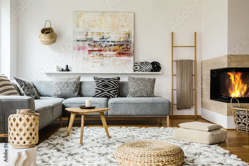 Wooden Table Next To Grey Corner Settee In Warm Living Room Interior With  Painting And Fireplace