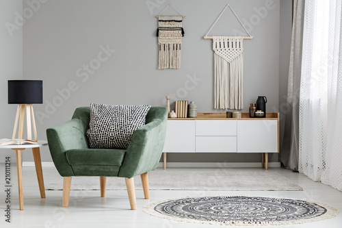 Foto op Canvas Restaurant Simple, white and gray living room interior with a sofa between a wooden table and cupboard. Real photo