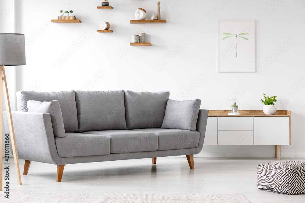 Fototapety, obrazy: Simple, gray sofa standing next to a white cupboard in living room interior with decorations on wooden shelves. Real photo