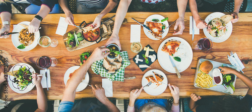 Family or friends summer party or outdoor dinner. Flat-lay of group of people at big table in cafe eating verious food together. Summer gathering or celebration concept