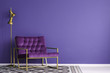canvas print picture - Ultra violet armchair with golden details and lamp standing on the empty wall