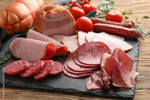 Fotografia Assortment of delicious deli meats on slate plate