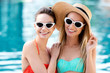 smiling young embracing women in vintage sunglasses standing at poolside and looking at camera