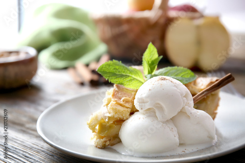 Fotografia, Obraz  Plate with piece of delicious apple pie and ice cream on wooden table, closeup