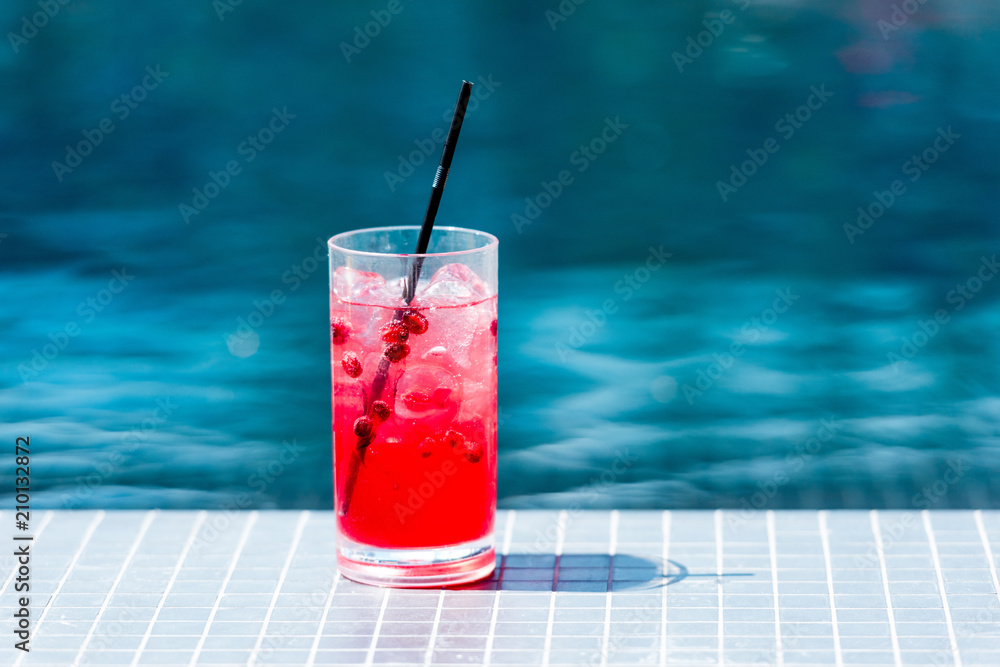 Fototapeta close-up shot of glass of red berry cocktail on poolside