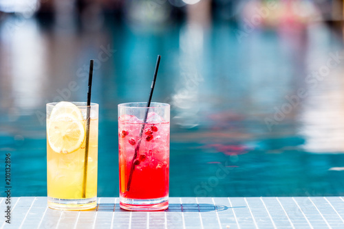 close-up shot of glasses of delicious red and orange cocktails on poolside Wallpaper Mural