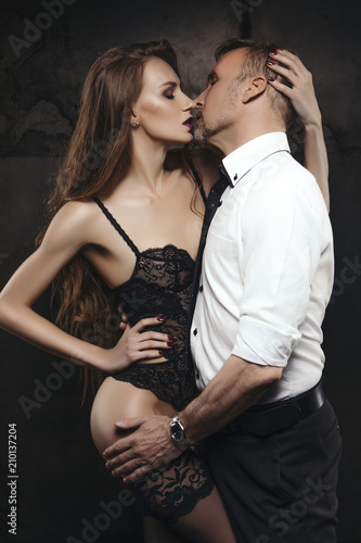 Photo Sexy young brunette woman with fit slim body and long curly hairstyle seduce old handsome rich business man