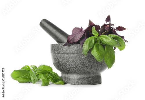 Mortar with fresh herbs and pestle on white background Fototapeta