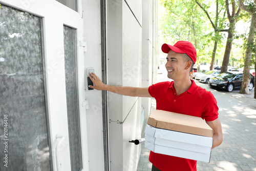 Young man with pizza boxes ringing the doorbell outdoors Tapéta, Fotótapéta