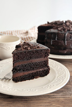 Plate With Piece Of Delicious Chocolate Cake On Wooden Table