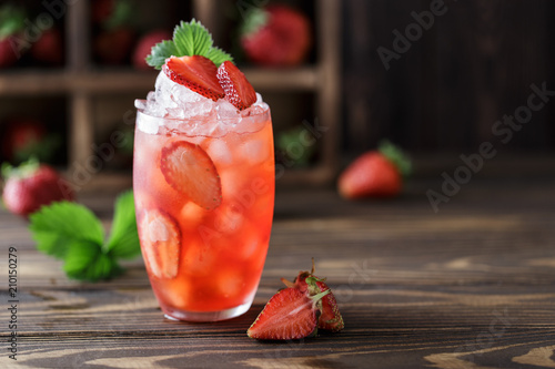 Fresh strawberry cocktail. Fresh summer cocktail with strawberry and ice cubes. Glass of strawberry soda drink on dark background.