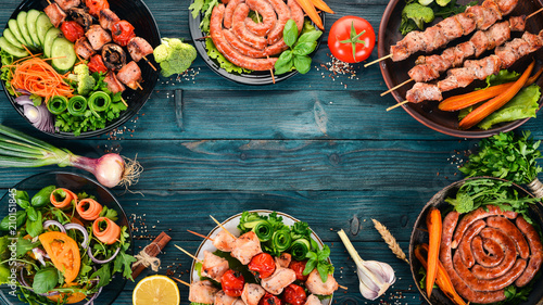 In de dag Eten A set of meats and fresh vegetables. Barbecue, sausages, steaks. On a blue wooden background. Copy space.