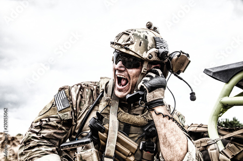 Special forces soldier, military communications operator or maintainer in helmet and glasses, screaming in radio during battle in desert Fototapeta