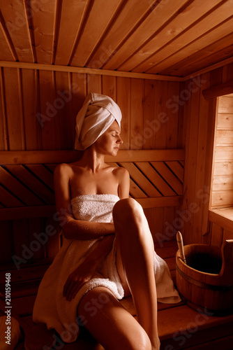 Photo  girl in a spa treatment in a traditional sauna with a brush for skin and a washcloth
