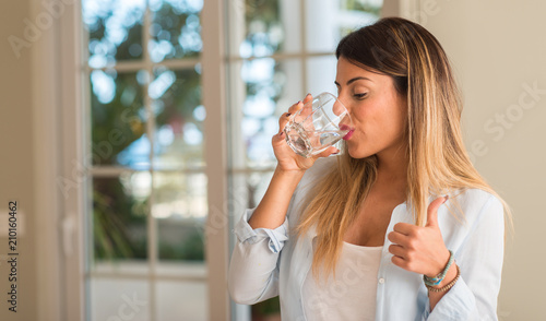 Beautiful young woman drinking a glass of water at home Fototapet