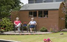 Two Women Sitting On A Garden ...