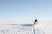 Driving Snowmobile Up A Snow M...