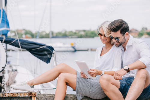 Fotografie, Tablou smiling young couple in sunglasses sitting and using digital tablet near yacht