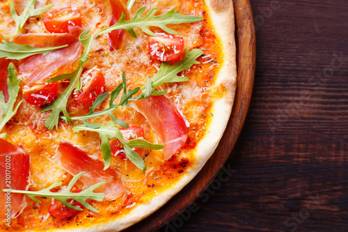 Restaurant, food delivery, pizzeria menu concept. Appetizing ham pizza with arugula flat lay with copy space. Delicious classical recipe, traditional Italian snack