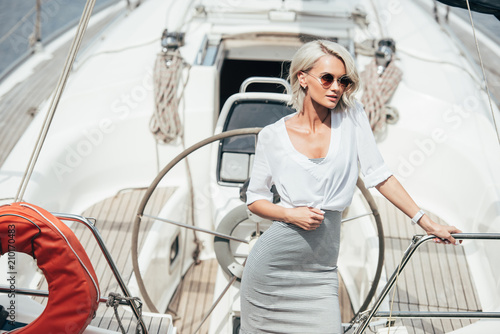 beautiful young blonde woman in sunglasses standing on yacht