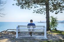 Man Sitting On A Bench By Lake Ontario, Toronto, Ontario, Canada