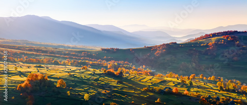 Extraordinary autumn landscape. Green fields with haystacks. Trees covered with orange and crimson leaves. Mountain landscapes.