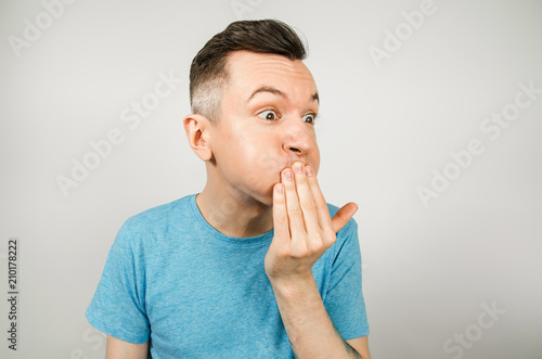 Young guy dressed in a blue t-shirt closing mouth from vomiting on a light background Tapéta, Fotótapéta
