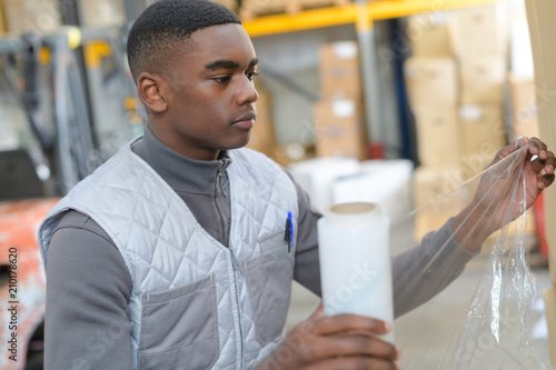 Photo  Warehouse worker holding roll of shrink wrap