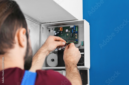 Photographie  Electrician installing alarm system
