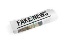 Rolled Newspaper With Headline FAKE NEWS On White Background