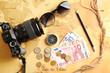 Photo camera, compass, sunglasses and money on world map. Travel planning concept