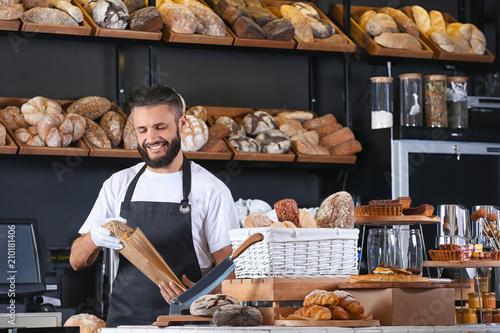 Spoed Fotobehang Bakkerij Young man packaging bread for customer in bakery