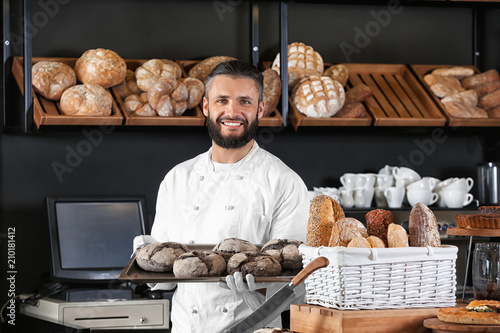 Male baker holding tray with fresh bread in shop