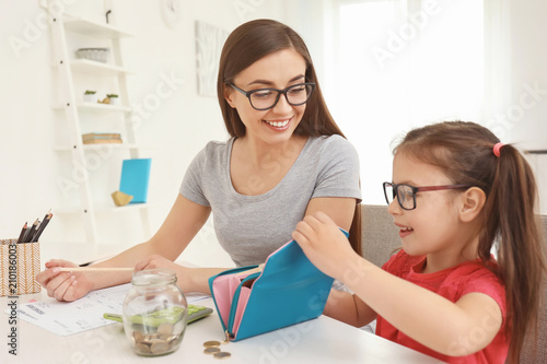 Fototapeta Happy little girl with her mother sitting at table and counting money indoors. Money savings concept obraz