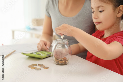 Fotografía  Little girl with her mother sitting at table and counting money indoors